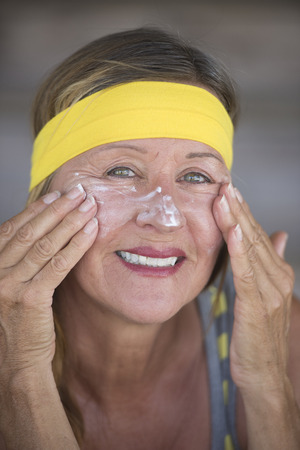 moisturiser: Portrait healthy fit active attractive mature woman with protective sunscreen skin care creme and moisturiser lotion on joyful smiling face, yellow headband, blurred background.