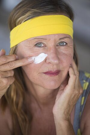 moisturiser: Portrait sporty fit active attractive mature woman with protective sunscreen skin care creme and moisturiser lotion on face, yellow headband, blurred background.