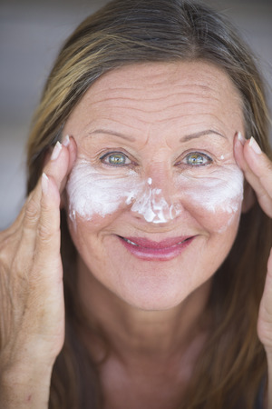 moisturiser: Portrait sporty fit active attractive mature woman with protective sunscreen skin care creme and moisturiser lotion on happy smiling face, blurred background. Stock Photo