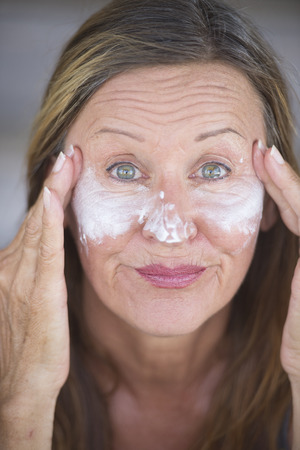 moisturiser: Portrait fit active attractive mature woman with protective skin care creme and moisturiser lotion on happy smiling face, blurred background. Stock Photo
