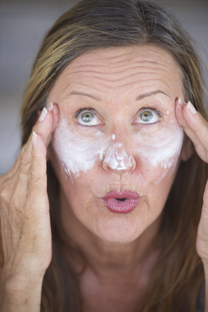 moisturiser: Portrait sporty fit attractive mature woman with protective skin care creme and moisturiser lotion on happy smiling face, blurred background. Stock Photo