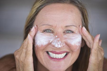 cheerful woman: Retrato deportiva atractiva mujer madura activa con crema de cuidado de la piel protectora y crema hidratante en la cara sonriente feliz, fondo borroso.