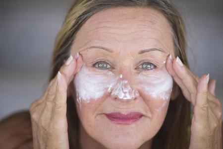 masajes faciales: Retrato deportivo mujer atractiva activa en forma madura con crema de cuidado de la piel protectora y crema hidratante en la cara sonriente feliz, fondo borroso.