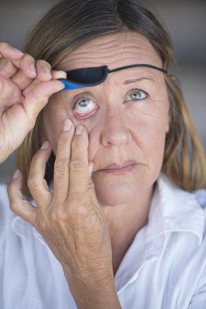 Portrait attraktive, reife Frau Heben Augenklappe als Schutz nach der Verletzung, unscharfen Hintergrund getragen.