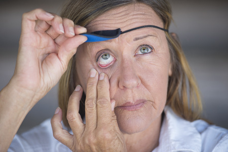 Portrait stressed attractive mature woman lifting eye patch worn as protection after injury, blurred background photo