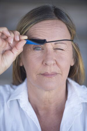 Portrait confident attractive mature woman lifting eye patch worn as protection after injury, blurred background.