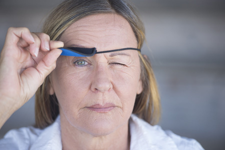 Portrait confident relaxed attractive mature woman lifting eye patch worn as protection after injury, blurred background. photo