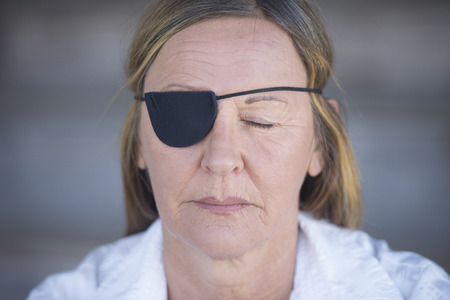 Portrait attractive mature woman wearing eye patch as protection after injury, closed eyes, blurred background. photo