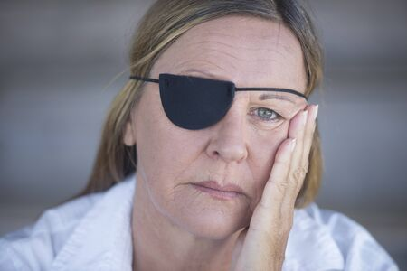 Portrait depressed attractive mature woman wearing eye patch as protection after injury, closed eyes, blurred background. photo