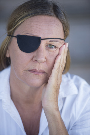 Portrait stressed attractive mature woman wearing eye patch as protection after injury, closed eyes, blurred background. photo
