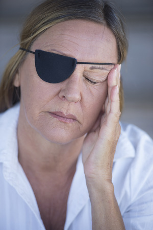 Portrait tired attractive mature woman wearing eye patch as protection after injury, closed eyes, blurred background. photo