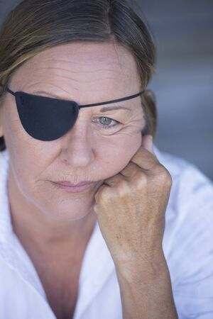 Portrait sad attractive mature woman wearing eye patch as protection after injury, closed eyes, blurred background. photo