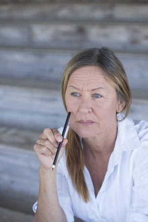 senior business: Portrait smart confident creative attractive mature business woman, thoughtful, serious, with pen in hand at lips, blurred background, copy space