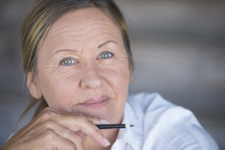 serious woman: Portrait confident creative attractive mature business woman, thoughtful relaxed smiling, with pen in hand, blurred background, copy space.