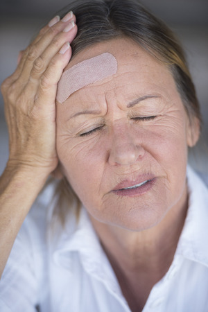Portrait attractive stressed mature woman in pain, headache, with  aid on injured forehead, closed eyes, blurred background. photo