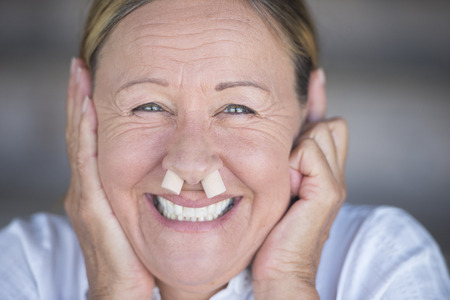 Portrait happy funny friendly attractive mature woman joyful smiling with nose plugs, blurred background.
