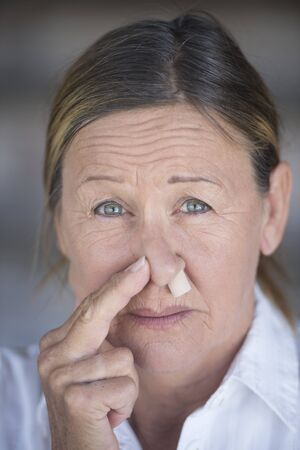 nose plugs: Portrait unhappy mature woman in pain, with protective nose plug, blurred background.