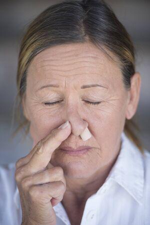 ojos cerrados: Retrato mujer madura infeliz en el dolor, con tap�n protector de la nariz, los ojos cerrados, fondo borroso.