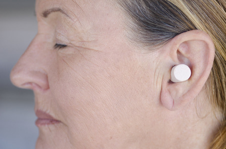 blocking: Profile Portrait attractive senior woman blocking sound with ear plug and closed eyes.