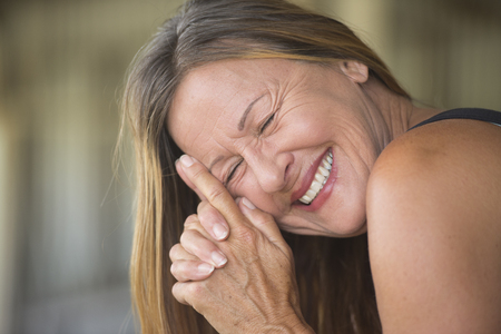 Portrait attractive mature woman smiling laughing joyful happy relaxed, closed eyes, copy space, blurred background.