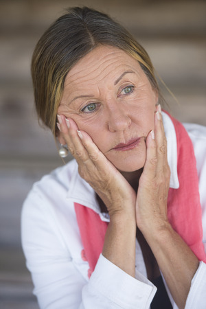Portrait attractive mature woman with anxious, sad, concerned expression, thoughtful, lonely, blurred background. photo