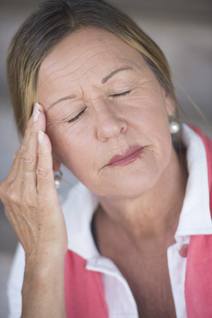 closed eyes: Portrait stressed attractive mature woman with headache, painful migraine, menopause, closed eyes, blurred background. Stockfoto