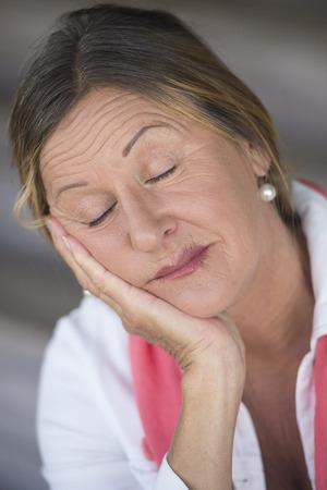 ojos cerrados: Retrato atractiva mujer madura cansado, los ojos cerrados, desgastado, reflexivo, sereno, con la barbilla apoyada en la mano, fondo borroso.