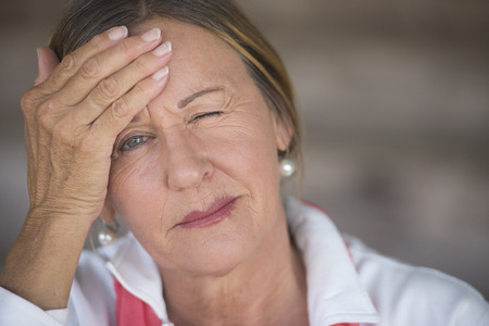 MENOPAUSE: Portrait attractive mature woman with headache, painful migraine, stressful menopause, one closed eye, blurred background, copy space.