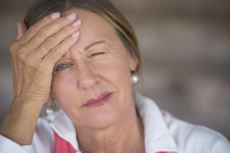 Retrato atractiva mujer madura con dolor de cabeza, migraña dolorosa, la menopausia estresante, un ojo cerrado, fondo borroso, copia espacio. Foto de archivo - 39411642