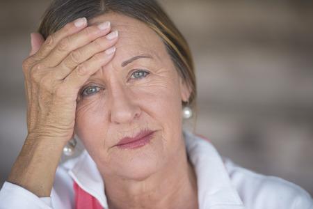 mujer sola: Retrato atractiva mujer madura con dolor de cabeza, migra�a dolorosa, la menopausia estresante, fondo borroso, copia espacio.