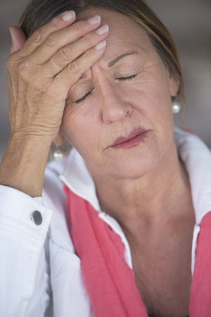 MENOPAUSE: Portrait attractive mature woman with headache, migraine, stressful menopause, closed eyes, blurred background. Stock Photo