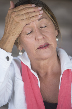 Portrait attractive mature woman with headache, painful migraine, stressful menopause, closed eyes, blurred background.