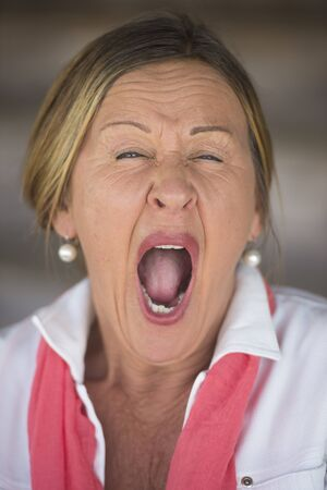 yawning: Portrait attractive elegant mature woman tired and yawning, blurred background. Stock Photo