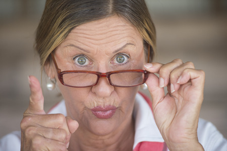 Potrait smart attractive mature business woman or dominant teacher with glasses and angry upset expression, blurred background.