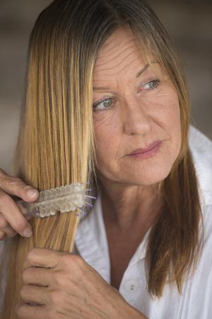 laid back: Portrait elegant attractive mature woman brushing long brunette hair, white shirt, blurred background.