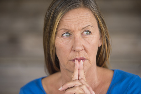 serenety: Portrtait attractive religious christian mature woman praying with folded hands, thoughtful, hopeful, meditating, blurred background, copy space. Stock Photo