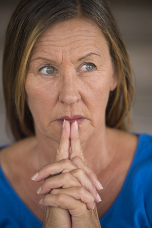 serenety: Portrtait attractive religious mature woman praying with folded hands, thoughtful, hopeful, meditating, blurred background.