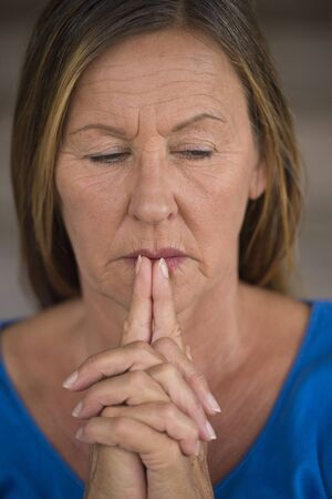 serenety: Portrtait attractive religious mature woman praying with folded hands, thoughtful, worried, meditating, blurred background. Stock Photo