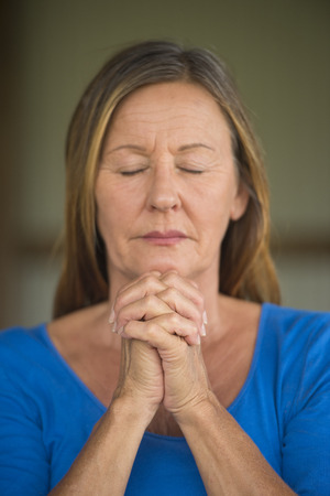 serenety: Portrtait attractive religious mature woman praying, with focus on folded hands, thoughtful, concentrated, meditating, closed eyes, blurred background.