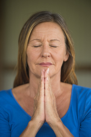 serenety: Portrtait happy attractive religious mature woman praying with focus on folded hands, thoughtful, meditating, closed eyes, blurred background.
