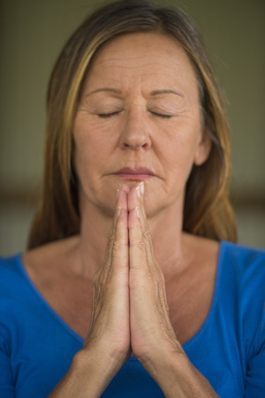 believing: Portrtait attractive religious mature woman praying with focus on folded hands, thoughtful, serene, meditating, closed eyes, blurred background. Stock Photo