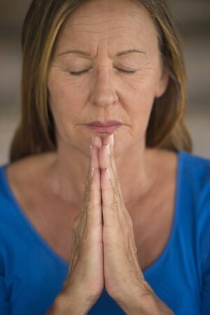serenety: Portrtait attractive religious mature woman praying with focus on folded hands, thoughtful, peaceful, meditating, closed eyes, blurred background. Stock Photo