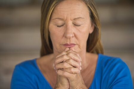 serenety: Portrtait attractive religious senior woman praying with focus on folded hands, thoughtful, meditating, closed eyes, blurred background. Stock Photo