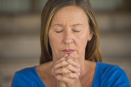 hoping: Portrtait attractive religious mature woman praying with folded hands, thoughtful, meditating, closed eyes, blurred background.