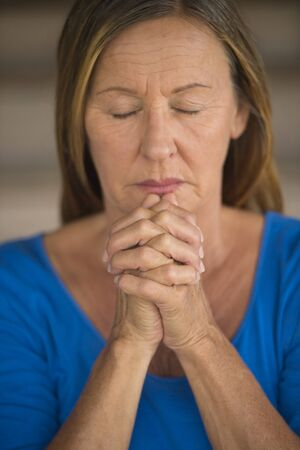 serenety: Portrtait attractive religious mature woman praying with focus on folded hands, thoughtful, meditating, closed eyes, blurred background.
