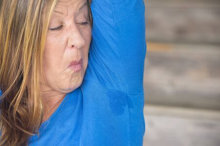 smelly: Portrait mature woman with sweat perspiration under arm with smelly wet moisture spot on blue shirt, blurred background, copy space.