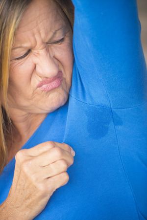 embarassed: Portrait angry mature woman with sweat perspiration under arm with wet moisture spot on blue shirt, blurred background, copy space. Stock Photo