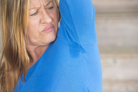 embarassed: Portrait angry mature woman with smelly sweat perspiration under arm with wet moisture spot on blue shirt, blurred background, copy space. Stock Photo