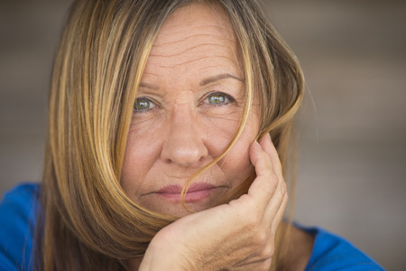 Portrait attractive mature lady in relaxed confident pose, happy serious look, blurred background, copy space.