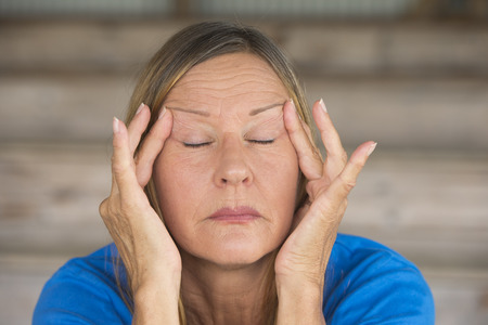 closed eye: Portrait attractive mature woman with migraine headache in pain, with closed eyes, finger at forehead, blurred background.